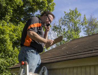 Roof Contractor Inspecting Roof After Hail Damage